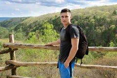 Toeristenmens met rugzak in bergen en bos wandelingssleep die in de zomertijd reizen Stock Fotografie