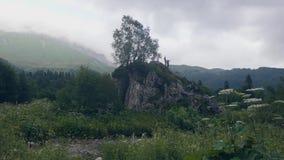 Toeristenmensen die zich bovenop klip in bergen bevinden en van mening van aard genieten stock video