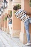 Toeristenpaar het spelen huid-en-zoekt onder kolommen Stock Foto
