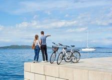 Toeristenpaar, man en vrouw met fietsen op hoog bedekte steenstoep dichtbij zeewater op zonnige dag stock foto