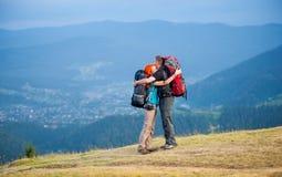 Toeristenpaar met rugzakken op de weg in de bergen Royalty-vrije Stock Foto's