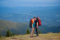 Toeristenpaar met rugzakken op de weg in de bergen Stock Afbeelding