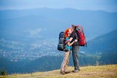 Toeristenpaar met rugzakken op de weg in de bergen Royalty-vrije Stock Foto