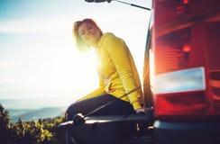 Toeristenreiziger het reizen in auto op groene bovenkant op berg, jong meisje glimlacht gelukkig tegen achtergrondzonsondergang i stock foto's