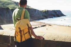 Toeristenreiziger met gele rugzak die zich op groene bovenkant op berg, wandelaarmening van rug bevinden die op oceaan, mens kijk stock fotografie