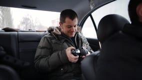 Toeristenritten in de winter binnenlandse taxis en het bekijken beelden op de camera Toeristenpassagier die nog het bekijken glim stock videobeelden