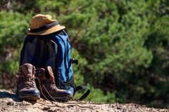 Toeristenrugzak, wandelingslaarzen en hoed op de open plek in pijnboombos Royalty-vrije Stock Foto