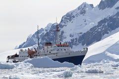 Toeristenschip onder de ijsbergen op de achtergrond van mountai Stock Afbeeldingen