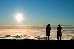 Toeristensilhouet het letten op zonsondergang op de bovenkant van Haleakala volc Stock Afbeeldingen
