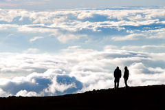 Toeristensilhouet het letten op zonsondergang op de bovenkant van Haleakala volc Stock Foto's