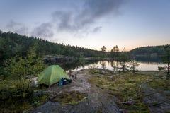 Toeristentent in de zonsondergang bij rotsachtig eiland van het meer van Ladoga stock afbeeldingen