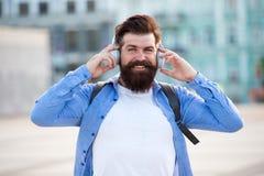 Toeristenvakantie Stedelijke achtergrond van de Hipster de moderne toerist Toeristen knappe hipster met rugzakhoofdtelefoons Mens royalty-vrije stock foto