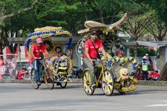 Toeristenvermaak - trishaw bij het zijn aangepast vervoer met drie wielen die, helder met kinderen` s beeldverhaal en bloemen wor stock foto's