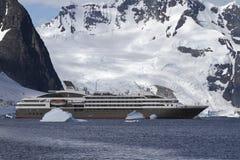 Toeristenvoering die onder ijsbergen in Antarctica op een backgrou varen Stock Foto's