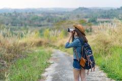 Toeristenvrouw die foto met haar camera in aard nemen royalty-vrije stock afbeeldingen
