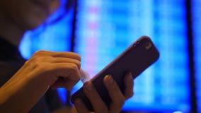 Toeristenvrouw die Haar Vluchttijd controleren die Mobiele Telefoon met behulp van dichtbij Vertrekraad in Luchthaven 4K Slowmoti stock videobeelden