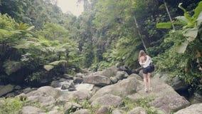 Toeristenvrouw die op rotsachtige rivier in tropisch regenwoud, mening van hommel lopen die erachter vliegen Jonge vrouw die binn stock footage