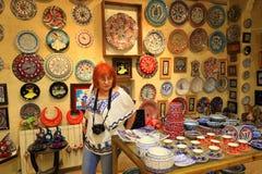 Toeristenvrouw die in Turkse aardewerkwinkel winkelen Royalty-vrije Stock Afbeeldingen