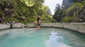 Toeristenvrouw gebruiken mobiel voor selfiefoto in mineraal bad van de thermische lente in openluchtkuuroord Reis die blogger doe stock videobeelden