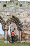 Toeristenvrouwen die de ruïnes van St Andrews waarnemen stock foto
