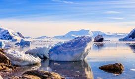 Toeristisch antarctisch cruiseschip onder de ijsbergen stock foto's