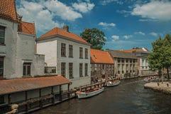 Toeristische boten en oude gebouwen op de kanaal` s rand in Brugge Stock Foto's
