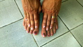 Toes and fingers with bi-color nailpolish on tile floor Royalty Free Stock Image