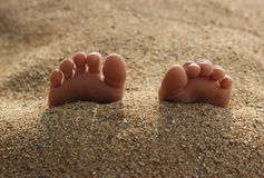 Toes in the Sand. A child's feet stick out of the sand royalty free stock photo
