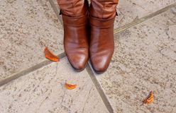 Toes of tan leather boots on a concrete Stock Photos