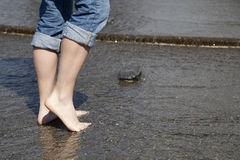 Toes in water. A woman enjoying the water by rolling up her jeans and walking around in the cool water Royalty Free Stock Photography