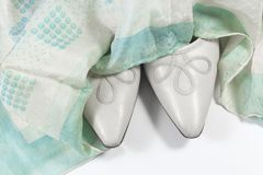 Toes of women`s vintage shoes draped in a faded blue and green silk scarf, on white. Horizontal aspect Royalty Free Stock Photos