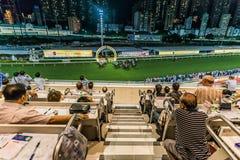 Toeschouwers die renbaan Hong Kon letten van de paardenkoersen op de Gelukkige Vallei Royalty-vrije Stock Foto
