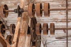 Toestellen en wielen op plafond in oud pakhuis Stock Fotografie
