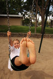 有他的脚toether的女孩在空气摇摆 免版税库存图片