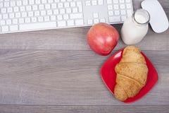 Toetsenbord op het bureau, het croissant, de yoghurt en de appelen Royalty-vrije Stock Foto's
