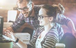 Toevallig bedrijfspaar die computer in het bureau met behulp van Twee collega's die aan een innovatief productontwerp samenwerken royalty-vrije stock foto's