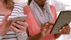 Toevallig commercieel team die tabletten en telefoons met behulp van stock videobeelden