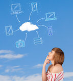 Toevallig meisje die wolk gegevensverwerkingsconcept bekijken op blauwe hemel Stock Foto's