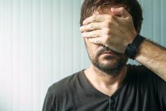 Toevallig volwassen mannetje die gezicht en ogen behandelen met hand Royalty-vrije Stock Afbeelding