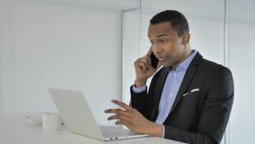 Toevallige Afro-Amerikaanse Zakenman Negotiating met Klant tijdens Telefoonbespreking stock video
