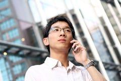Toevallige Aziatische zakenman die op zijn celtelefoon spreekt royalty-vrije stock afbeeldingen