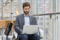 Toevallige bedrijfsmens die aan laptop in luchthavenzaal werken Stock Fotografie