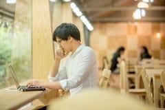 Toevallige bedrijfsmens die met laptop in koffie werken Stock Foto