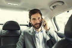 Toevallige bedrijfsmens op mobiele telefoon in achtergedeelte van de auto Royalty-vrije Stock Foto