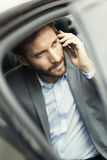 Toevallige bedrijfsmens op mobiele telefoon in achtergedeelte van de auto Stock Foto's