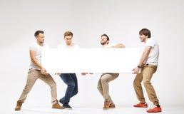 Toevallige geklede kerels die reusachtig aanplakbord dragen Stock Foto's