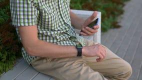 Toevallige geklede mens die zijn van gadgets slimme horloge en smartphone zitting op bank gebruiken stock footage