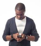 Toevallige geklede zwarte mens die zijn mobiele telefoon kijken Royalty-vrije Stock Fotografie