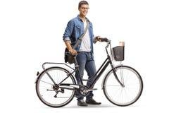 Toevallige jonge mens die zich met een fiets bevinden stock foto