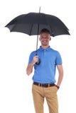 Toevallige jonge mens met in hand paraplu Stock Foto